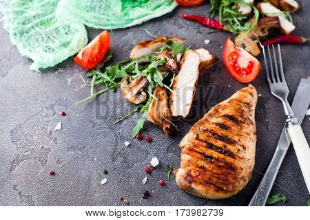 Lunch of sliced grilled chicken breast with vegetables and herbs on a stone table with a dark cloth, text