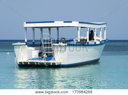 The wooden boat drifting by Roatan island (Honduras).