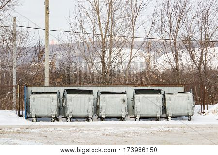 Five silver metal garbage containers in winter