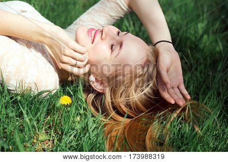 Blue-eyed Blonde Lying on the Grass with Dandelions. Cute Young Girfriend Lovely Laughing in Warm Sunny Day.