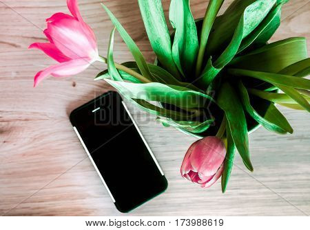 spring buquet of rose tulipans with phone wooden background