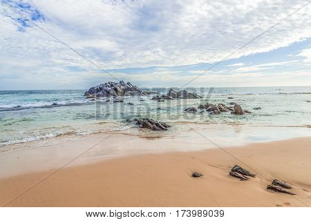 Beautiful lanscape of a sandy beach with rocks in the ocean against a blue sky background.