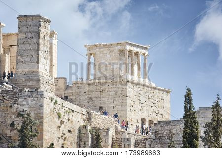 ATHENS, GREECE, SEPTEMBER 7, 2016: Tourists entering Acropolis of Athens by climbing the marble stairs.
