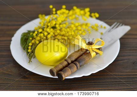 Easter table setting with plate, silverware, Easter egg and mimosa