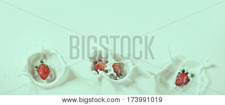Beautiful retro toned panoramic view of a range delicious strawberries sinking down into milk with a drops