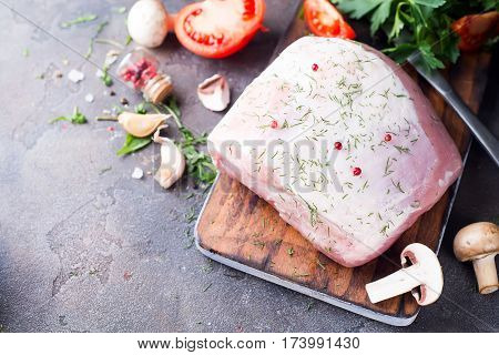 Raw tenderloin or sirloin with herbs and pepper beans with vegetables at the dark stone background, copy space