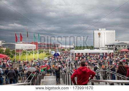 People outside Ice hockey arena. Minsk, Belarus - May 17, 2014: Ice hockey fans leaving the world championship arena in Minsk to enter the fan zone outside. Recognizable people and signs in the image.