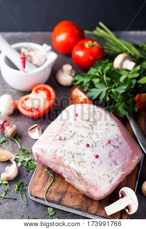 Raw tenderloin or sirloin with herbs and pepper beans with vegetables at the dark stone background,