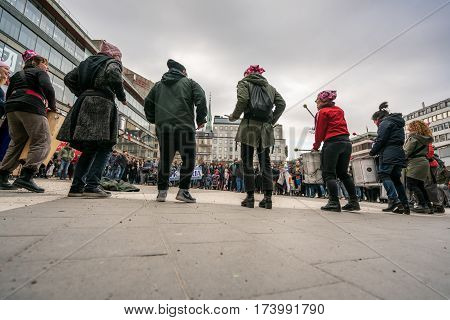 Group of females performing with drums. Stockholm, Sweden - January 01, 2017: Female street performers with drums playing at demonstration in Stockholm to support the protesters seen in the background