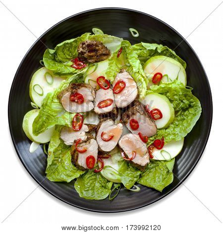 Pork salad on black plate, top view, isolated on white.