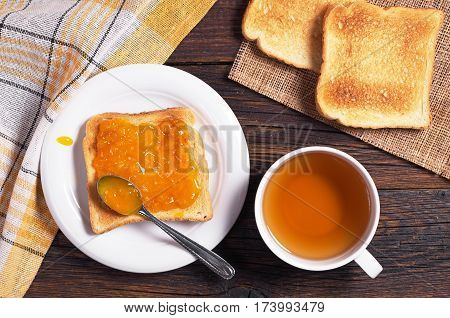 Cup of tea and toast with apricot jam on wooden table top view