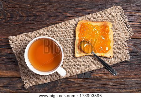 Tea cup and toasted bread with apricot jam on wooden table top view
