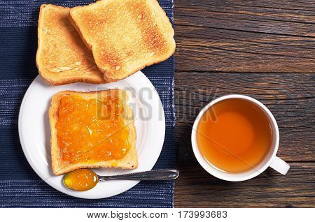 Tea cup and toasted bread with apricot jam on rustic wooden table top view