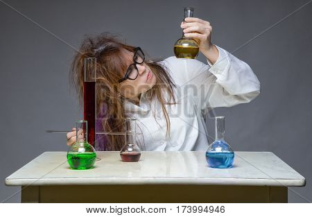 Working shaggy scientist in workspace on gray background