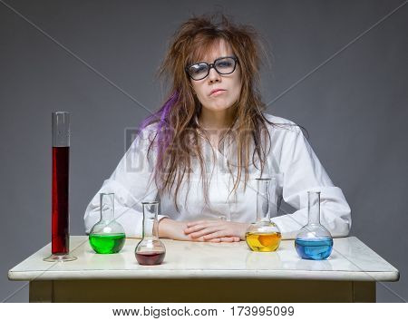 Serious shaggy scientist woman in lab on gray background