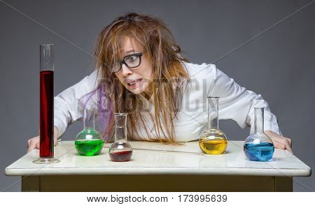 Surprised messy chemist in lab on gray background
