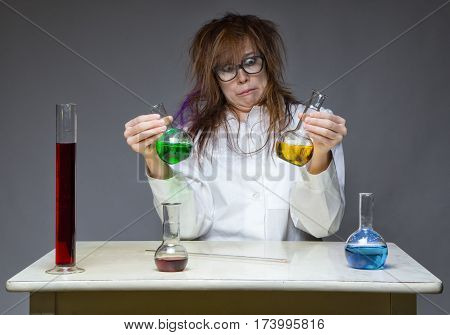 Choice and grimacing scientist in lab on gray background