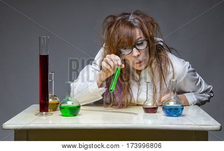 Shaggy scientist looking at glass flask in lab on gray background