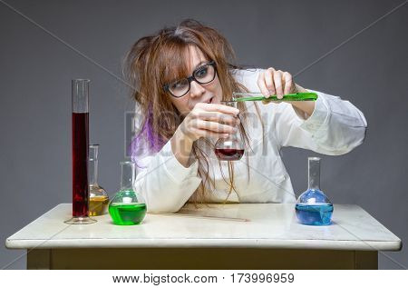Mixing liquid shaggy scientist in lab on gray background