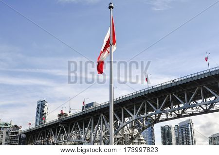 British Columbia,Canada-March 21 2017: Canada Flag and the Bridge in the back located in Granville Island at Vancouver,BC Canada