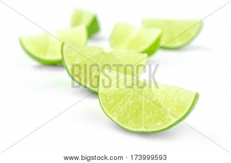 Scattering of fresh lime wedges isolated on white background cutout.