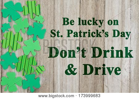 Saint Patrick's Day safety message Green shamrocks on weathered wood with text Don't Drink and Drive