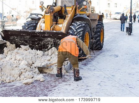 Janitor cleans the street of snow in the morning