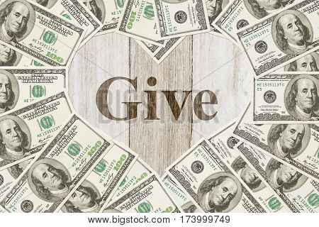 The love of donating money message One hundred dollar bill in the shape of a heart with a weathered wood heart with text Give