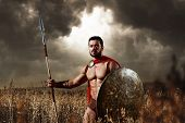 He knows no fear. Sepia toned shot of a Spartan warrior with strong muscular torso wearing red cape holding a spear and a shield walking through the field alone dramatic gloomy sky on the background poster