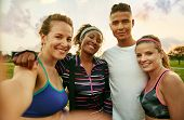 Smiley multicultural group of 4 people takes a group photo at sunrise in the park after their high intensity strenght training session poster