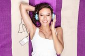 Happy woman listening to music through MP3 player using headphones while lying on picnic blanket poster