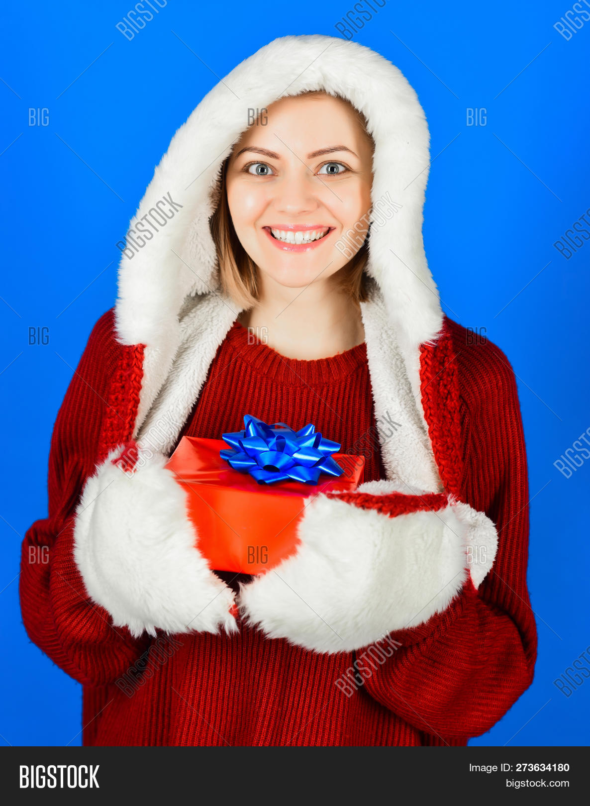 4e51b8c01afb1 Beauty Christmas fashion model girl with Christmas present. Happy woman in  fur hat holds X-mas gift box. Charming woman in Santa Claus hat with gift  box.