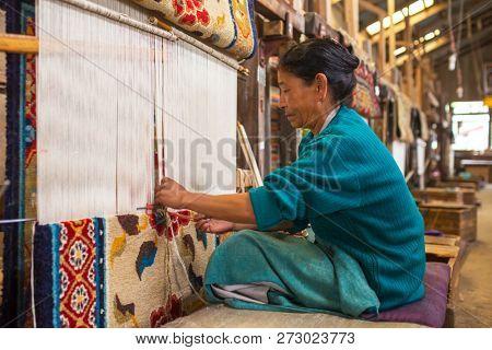 Darjeeling, India - April 19, 2017: Unidentified tibetan woman works as weaver in the carpet workshop of Tibetan Refugee Self Help Center, Darjeeling, India