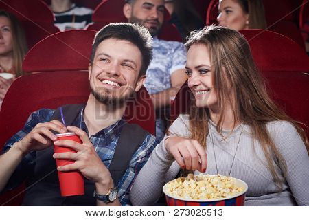 Happy Cute Couple Eating Popcorn And Laughing At Funny Comedy In Cinema Theater. Attractive Girl And