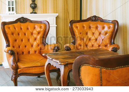 Classic Interior Room. Old Antique Leather Arm Chairs And Table. Classic Decoration With Elegant Fur
