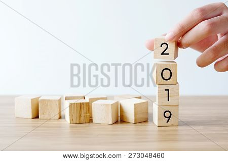 Hand Holding 2019 Happy New Year Wood Cubes On Table Background, 2019 New Year Greeting Card Banner