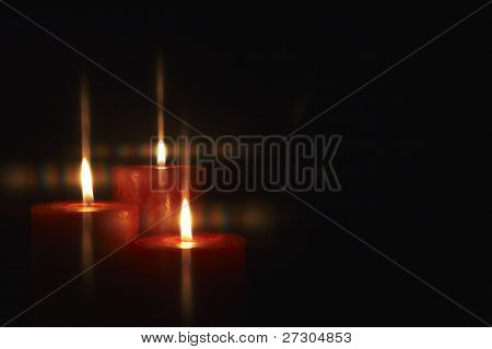 Closeup of burning candles isolated on black background