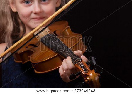Happy Little Blonde Girl Playing On Violin On Dark Background