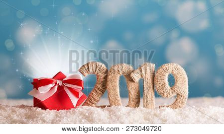 Inscription 2019 New Year And Red Box Of Magic In The Snow On Background With Bokeh Effect