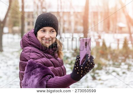 Young Happy Woman In Warm Purple Dawn Jacket Smiling While Making Selfie With Smartphone During Walk