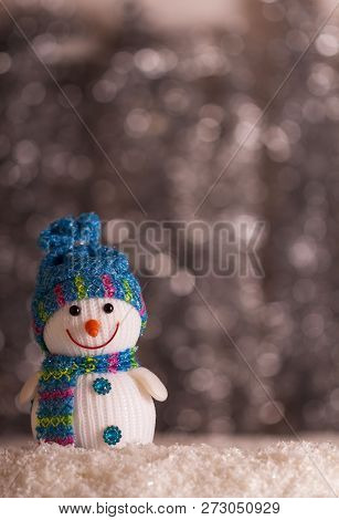 Smiling Snowman And Snowflakes On A Gray Background With Bokeh Effect