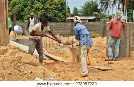 African Workers With Shovels Work At Site. Construction Industry In West Africa. Site In Ghana. Ghan