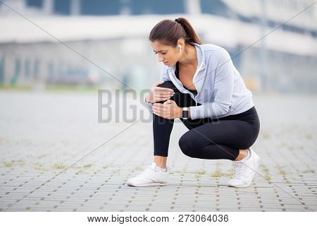 Fitness. Athletic women holding knee having a trauma poster