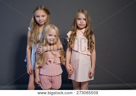 Three Beautiful Little Girls Sisters Portrait Fashion Grey Background