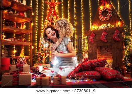 Cheerful Cute Curly Little Girl And Her Older Sister Exchanging Gifts. Sisters Having Fun Near Chris