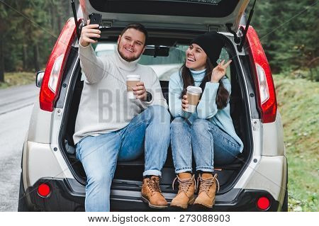 Man And Woman Stop To Drink Warm Up Tea And Taking Selfie In Car Suv Trunk. Road Trip Concept