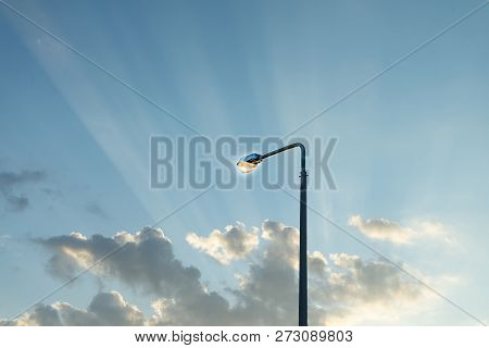 Lamppost On The Background Of The Evening Sky With The Rays Of The Setting Sun.
