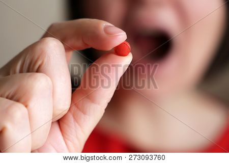 Girl Takes A Pill, Close-up. Woman Puts Red Tablet In Mouth, Sick Female Taking Medicines, Antidepre