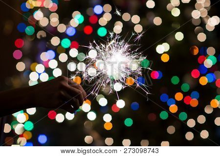 Burning Sparkler In Hand, Colorful Bokeh Spots Of A Christmas Tree In Dark Room.