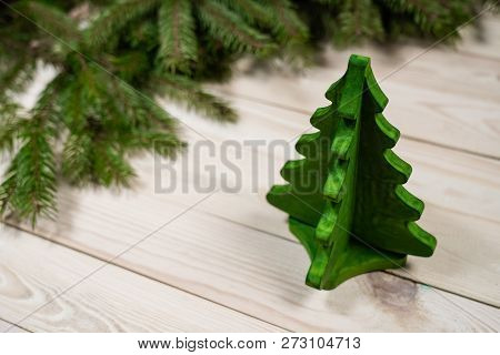 Miniature Toy Christmas Tree On A Wooden Table. Imitation Realistic Scene. The Model A Small Christm